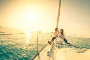 Happy couple in love on sail boat with champagne at sunset